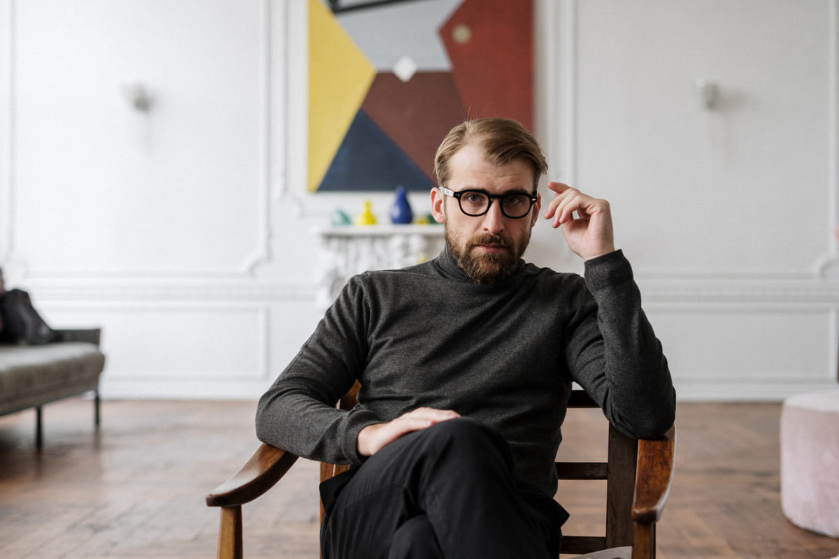 Canva - Man in Black Sweater Sitting on Brown Wooden Chair
