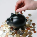 Canva - Person Holding Black Ceramic Pig Coin Bank